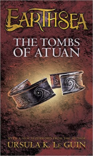 Dark brown cover of The Tombs of Atuan with a silver ring carved with waves and broken in two.